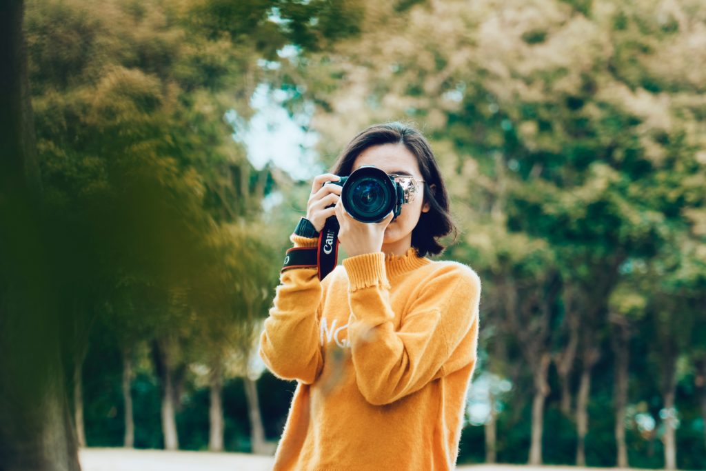 A photo of a girl holding a camera by Marco Xu on unsplash for a personal brand blog